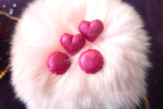 A decorative puff with pink miniature dessert on top.